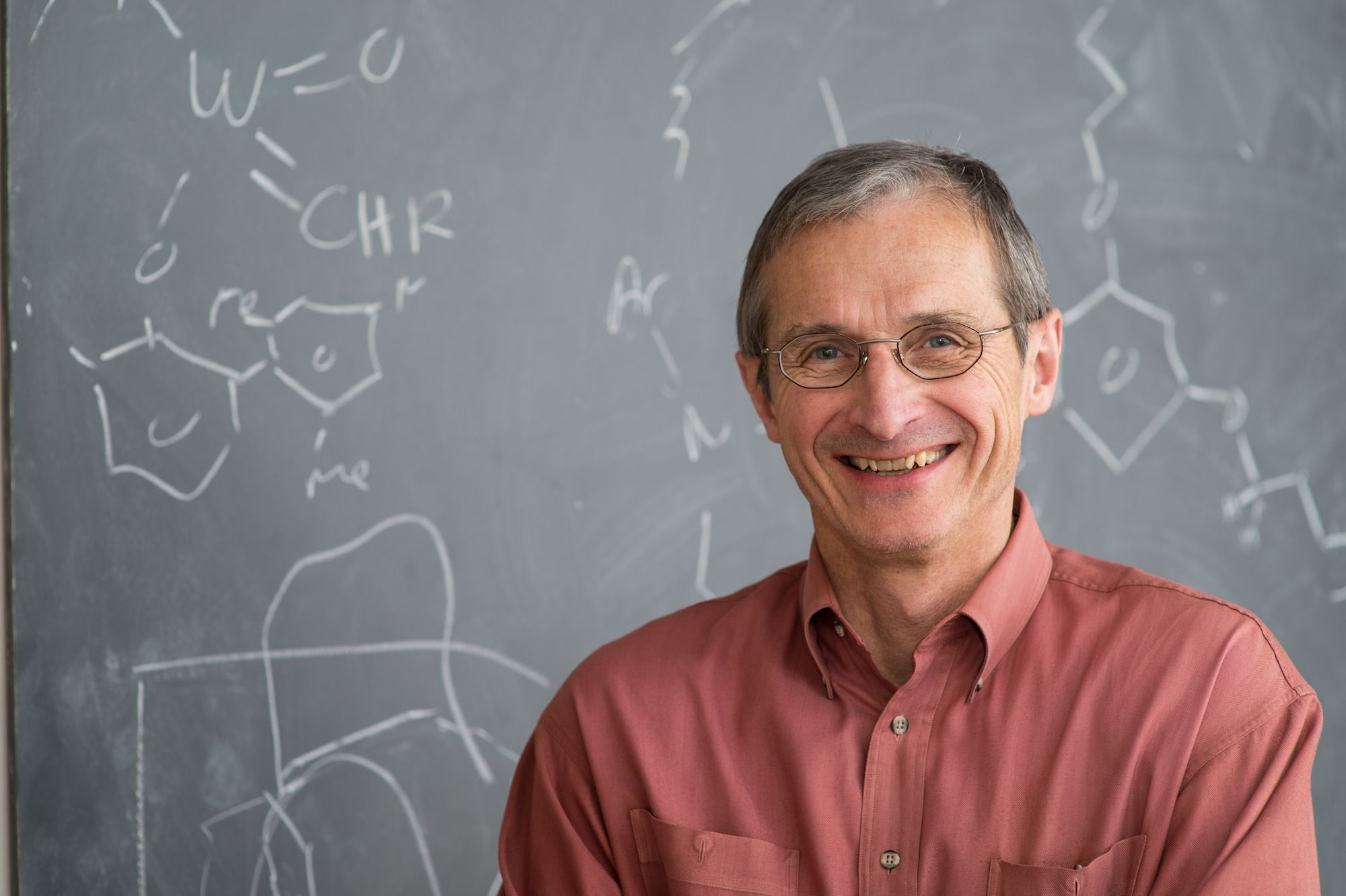 Professor Schrock smiles in front of a chalkboard of research