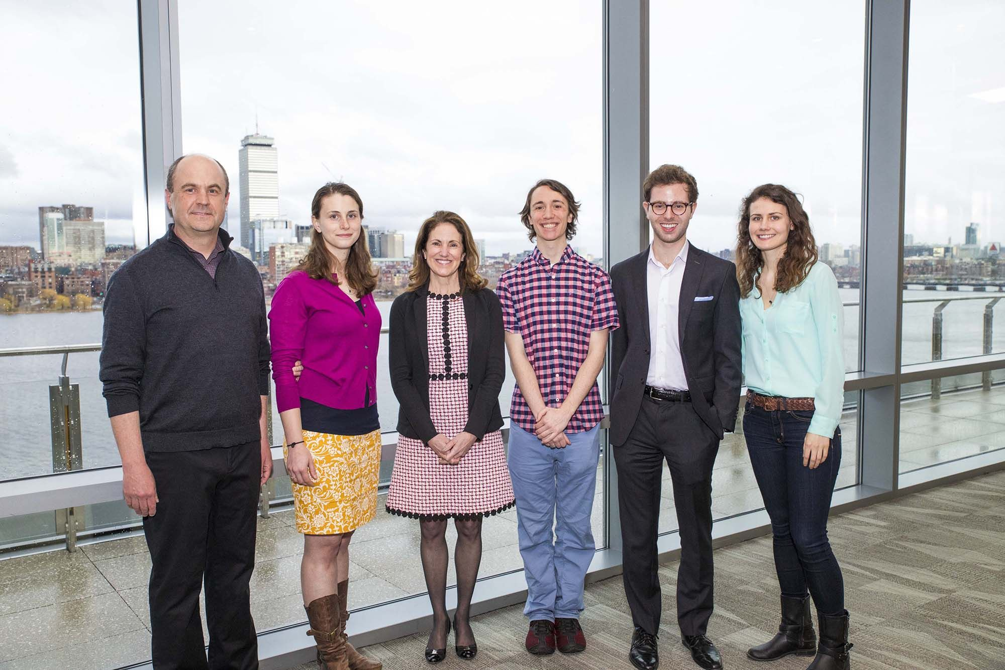 Winners of the 2018 Change Maker Award stand in a room with a view of the Boston skyline