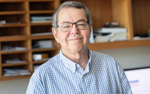 Professor Steve Buchwald smiles in his office.