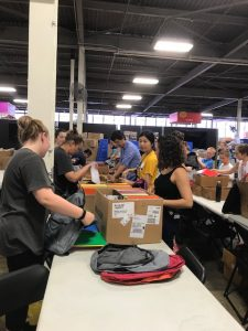 Members from the Department of Chemistry help assemble backpacks for Cradles to Crayons recipients.