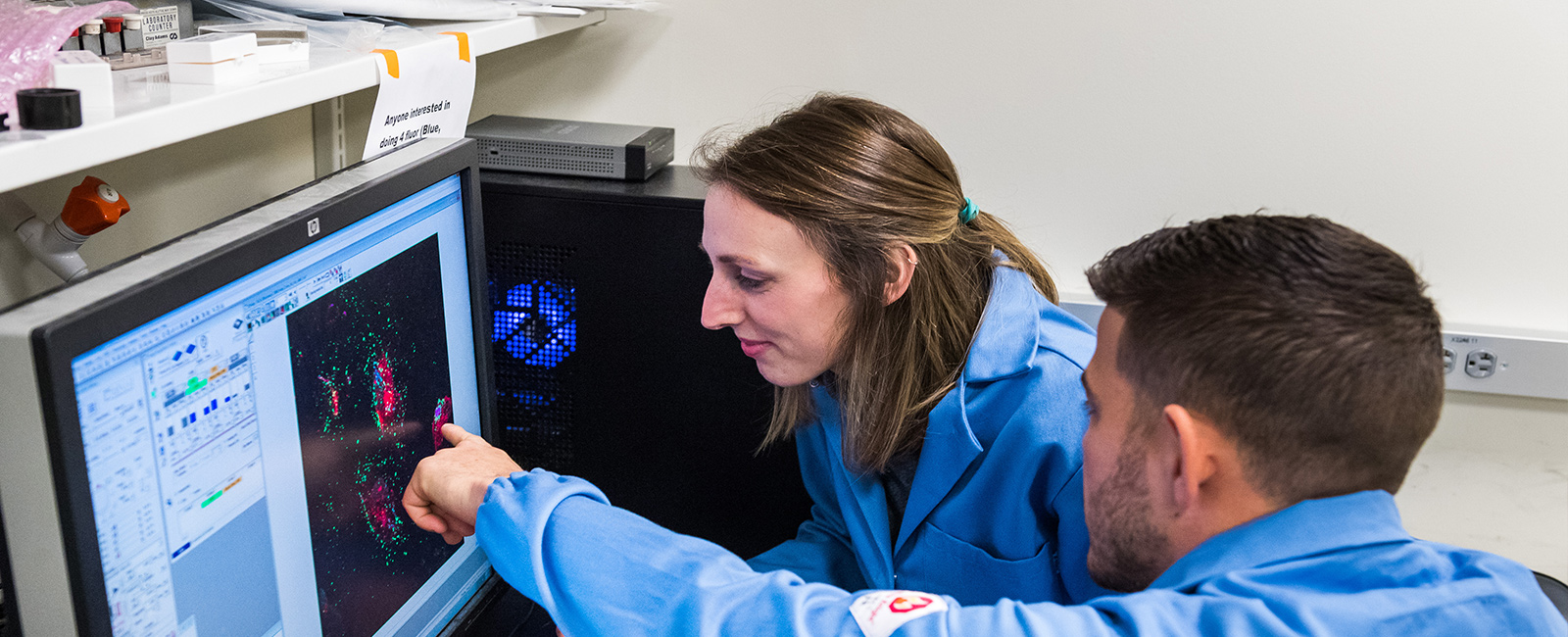 Two graduate students examine cells on a computer