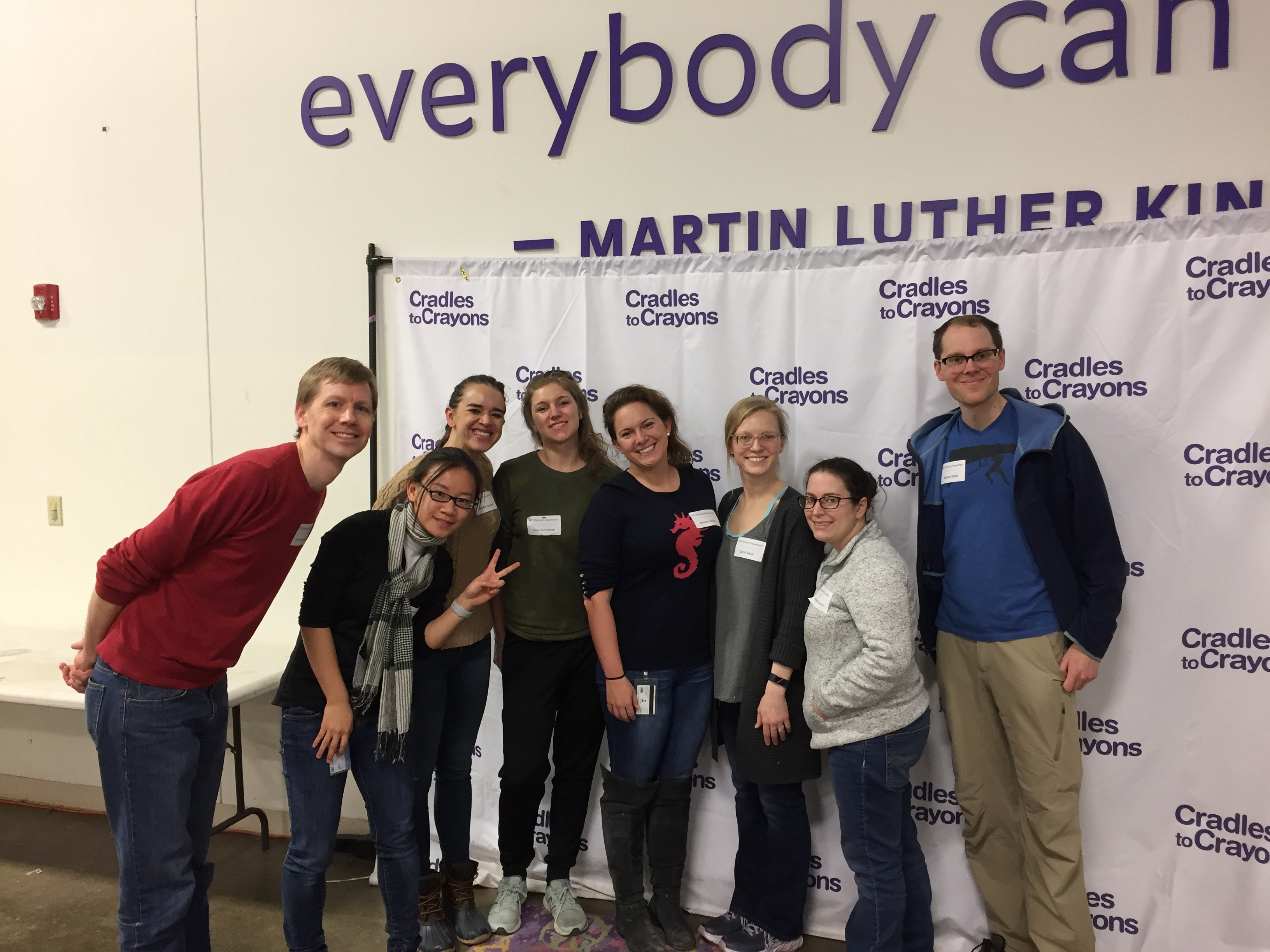 A group smiles while volunteering at a warehouse.