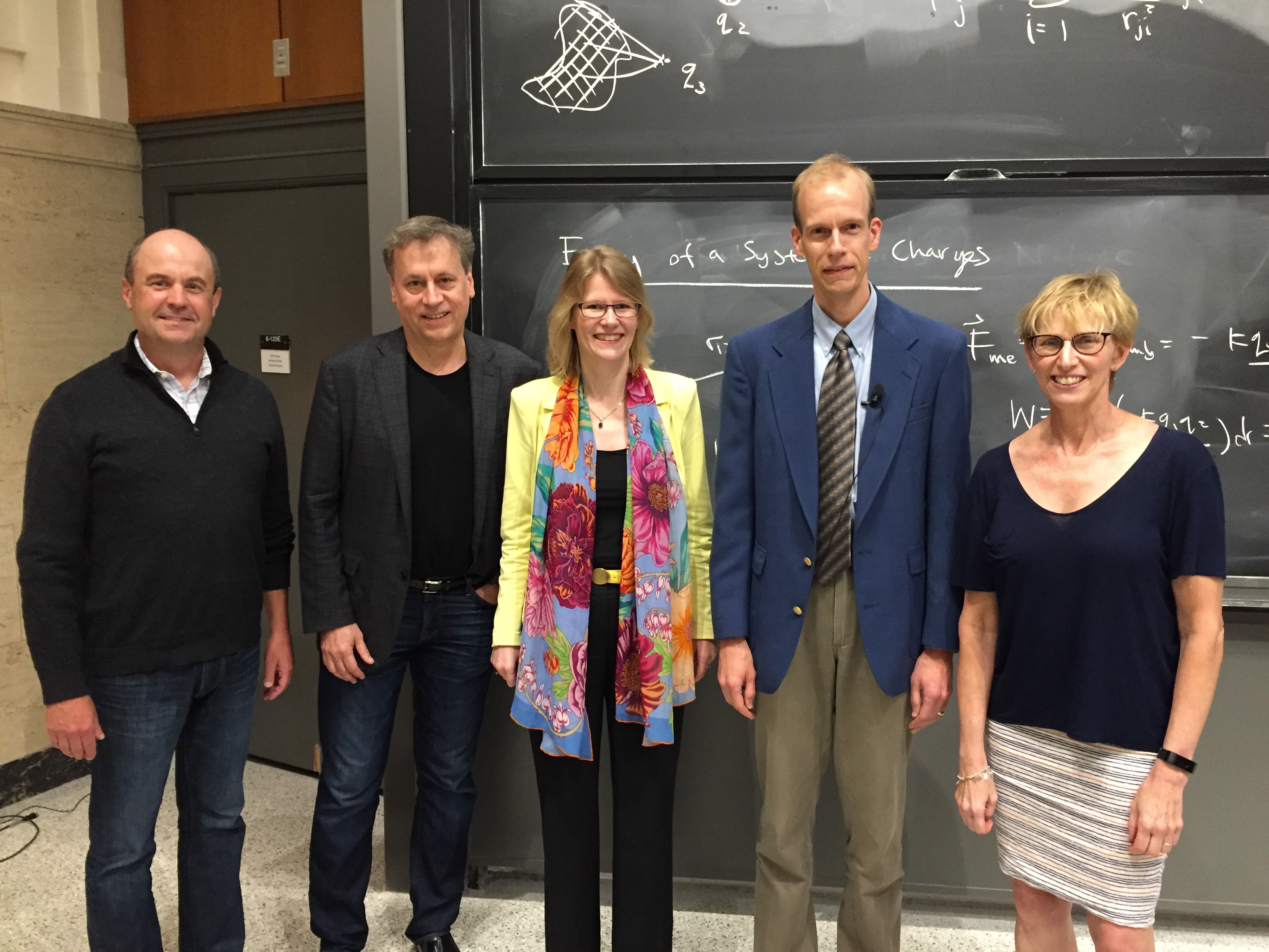 MIT Faculty and visiting speakers pose in a lecture hall.