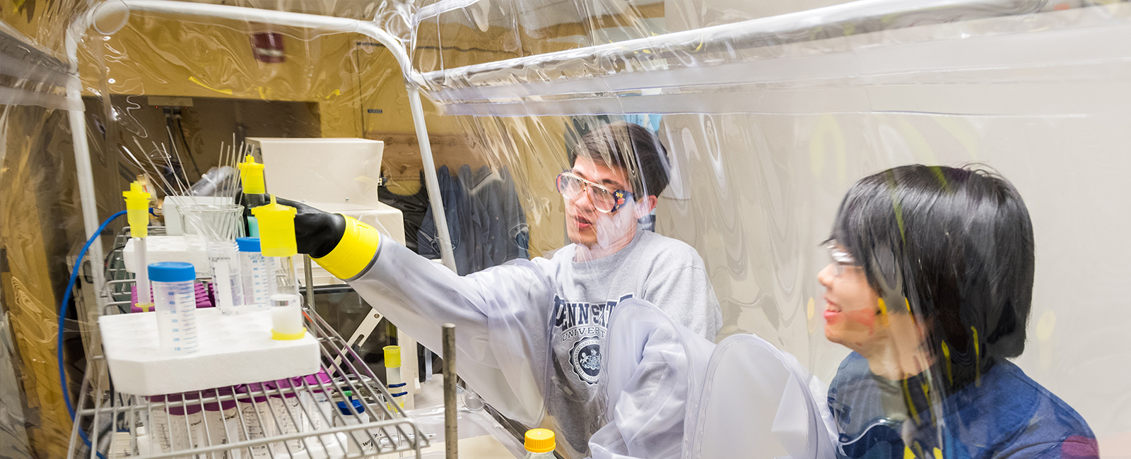 Two graduate students conduct research at a fume hood.
