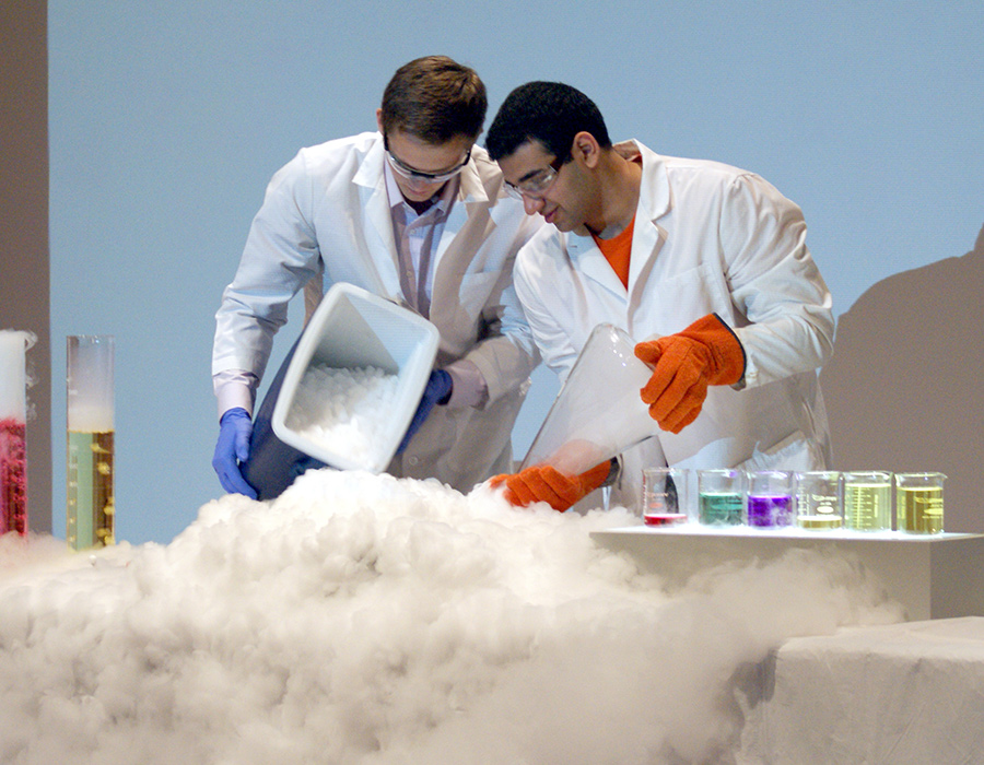 Two undergraduate students demonstrate a dry ice experiment before an audience of schoolchildren.