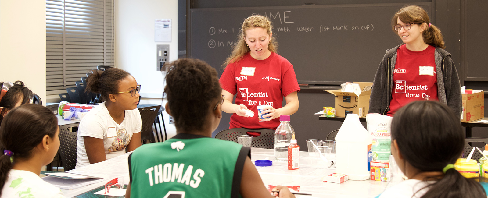 Two female graduate students lead a workshop of science demonstrations for middle school girls.