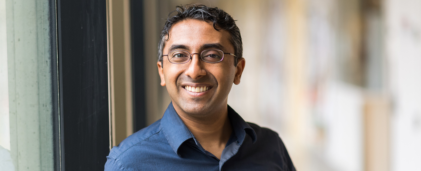 Yogesh Surendranath smiles in a hallway