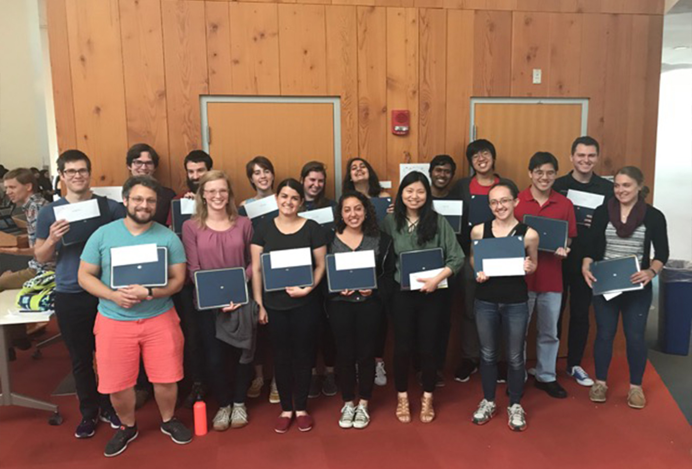 Graduate Students pose in rows with their Teaching Assistant Award certificates.