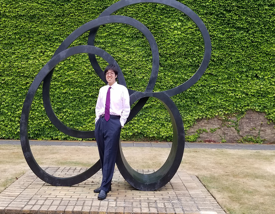 Graduate Student Henry Tran poses outdoors in front of a sculpture.