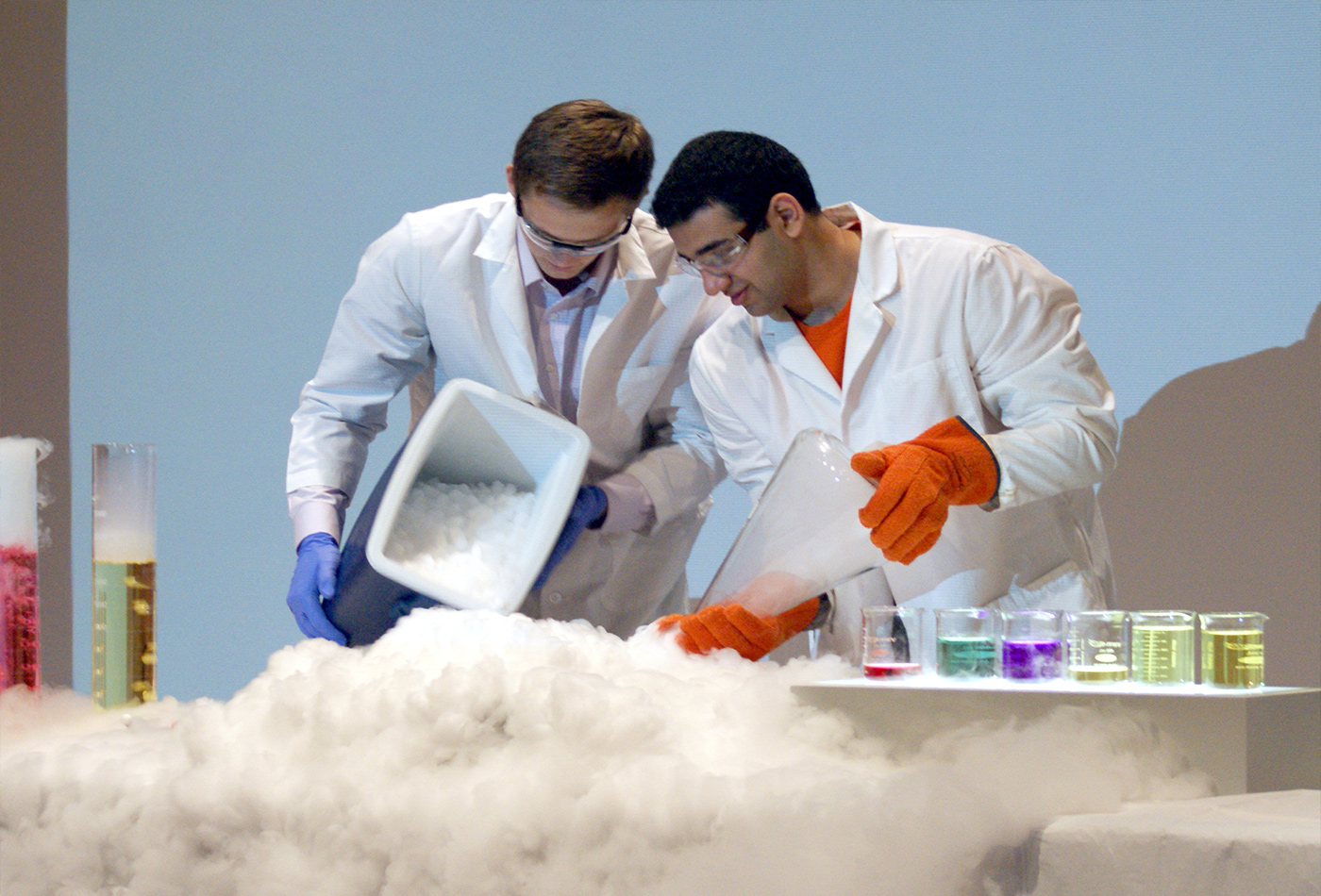 Two students pour out a container of smokey dry ice