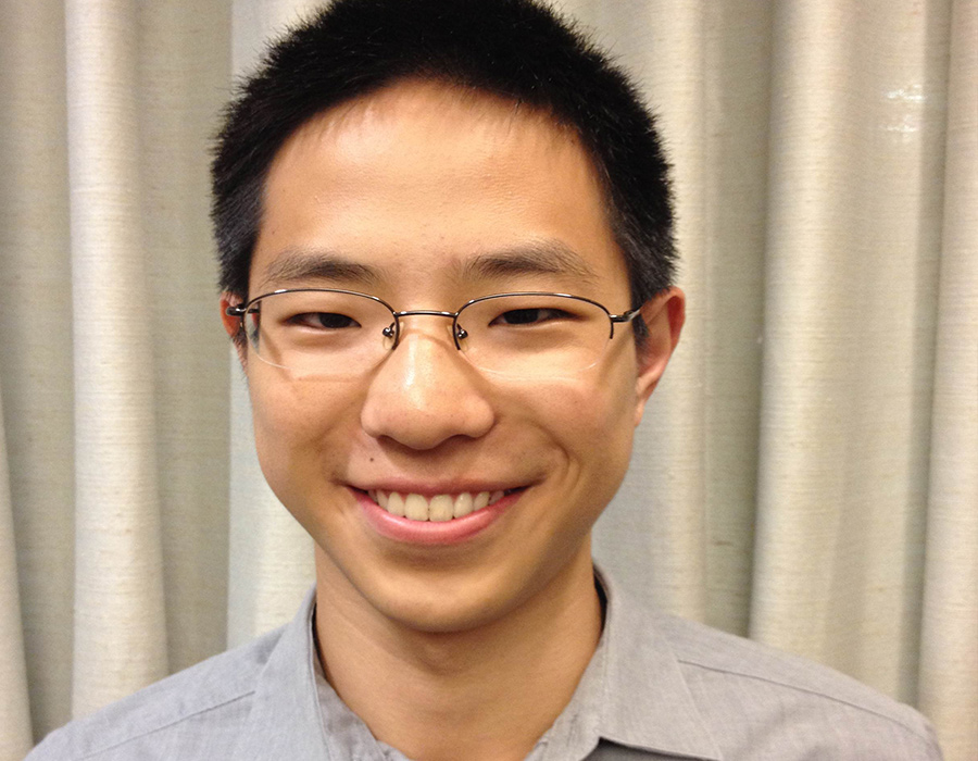 Chemistry alumnus Daniel Zhang poses in front of a cream curtain.