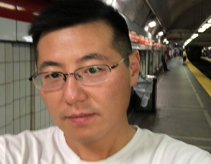 Postdoctoral researcher Wen Zhou stands on the subway platform.