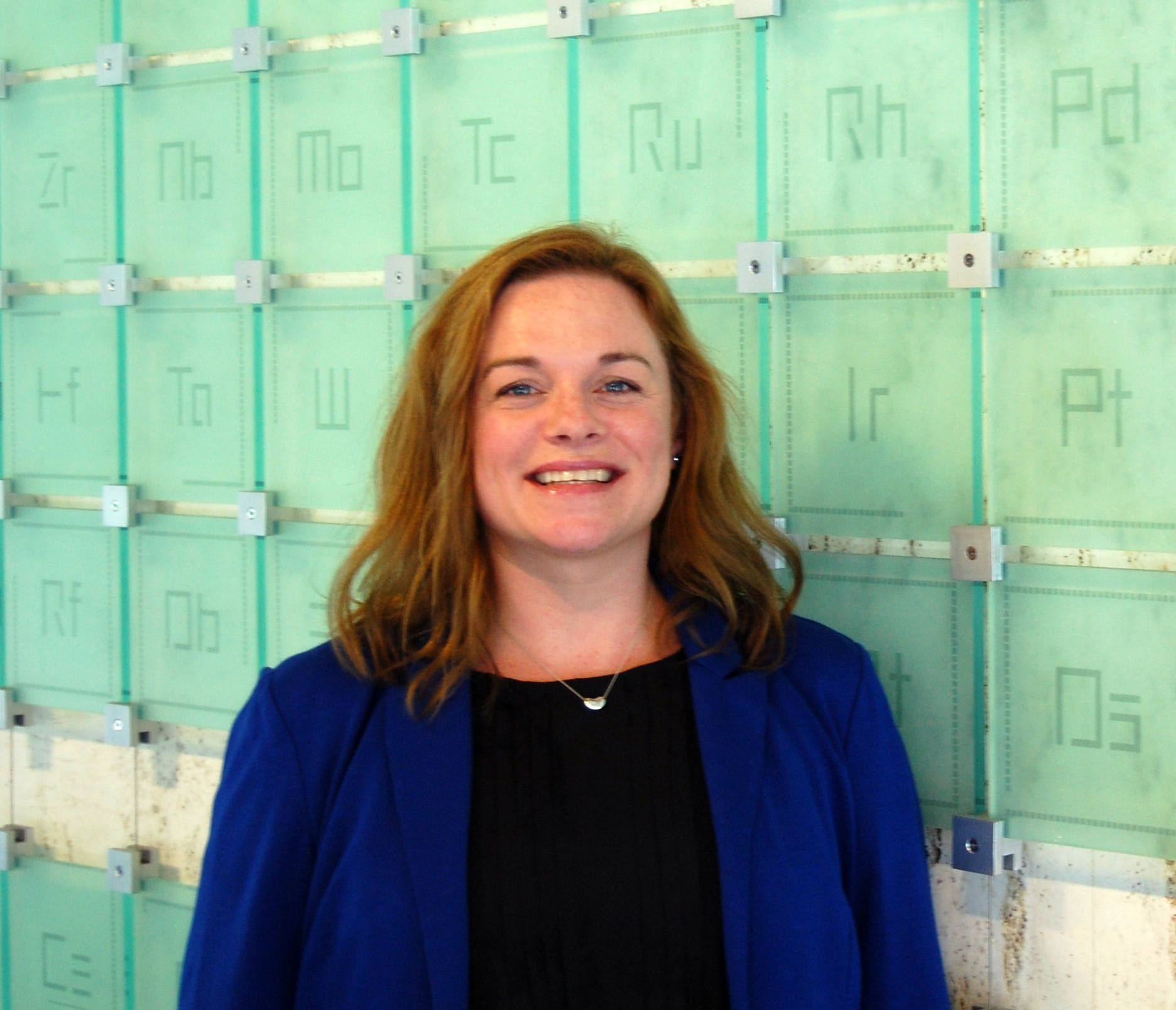 Macall Zimmerman smiles in front of a glass sculpture of the periodic table