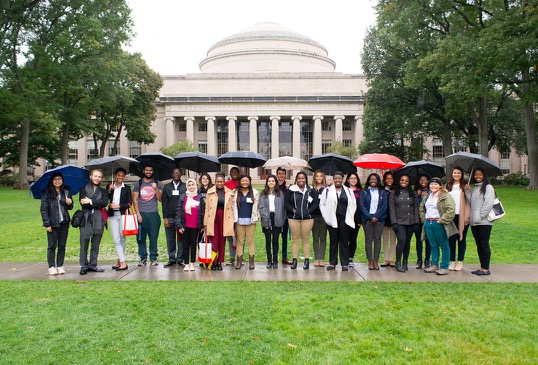 23 students stand under umbrellas in front of the MIT dome.