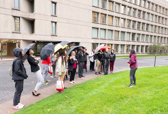 A group of students stand outdoors under umbrellas and listen to a guide while on a campus tour.