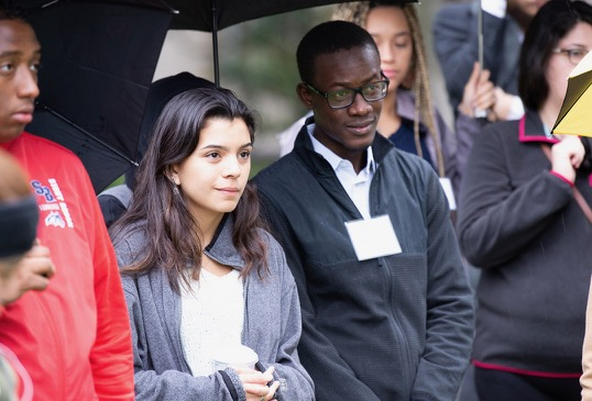A young man and a young woman listen to a guide as they enjoy a campus tour.