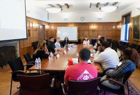 A group of students sit around a conference table with a panel of professors and professionals.