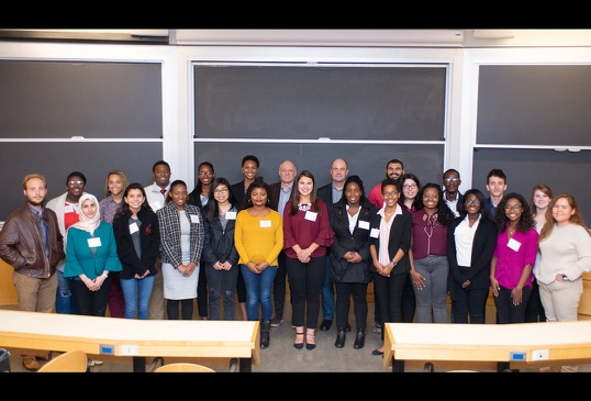 Two male professors pose with a group of 23 student program participants.