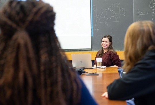 A seated female graduate student smiles as she addresses a conference table of program participants.