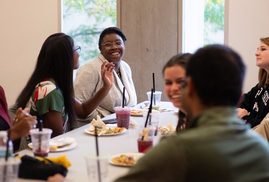 A group of young women engage in conversation around a breakfast table.