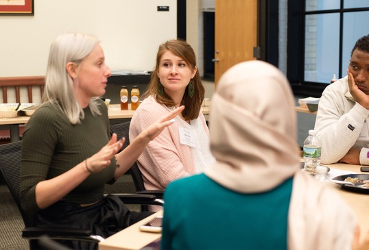 A female current MIT graduate students engages with two female program participants at lunch.