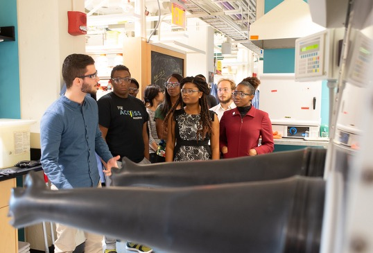 A male graduate student explains his pending demonstration to a group of graduate students in a lab.