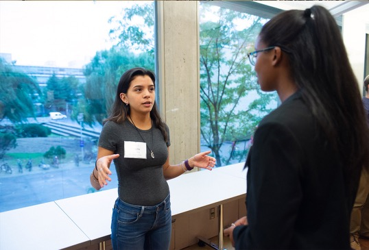 Two female program participants engage in conversation.