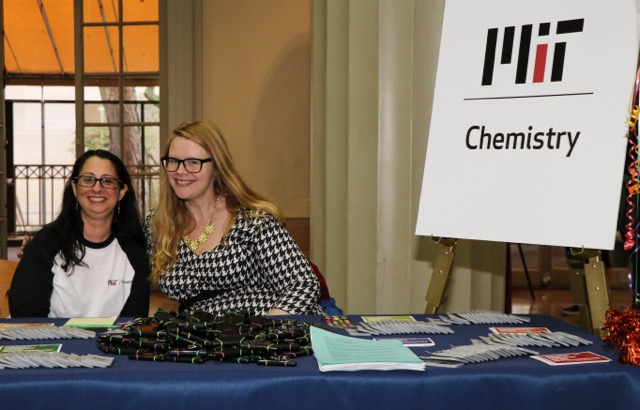 Two female staff members smile together at a table laden with promotional items.