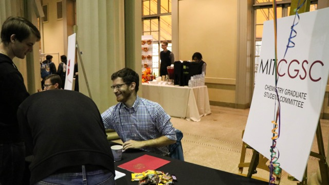 A male student sitting behind a table informs a student about an organization.