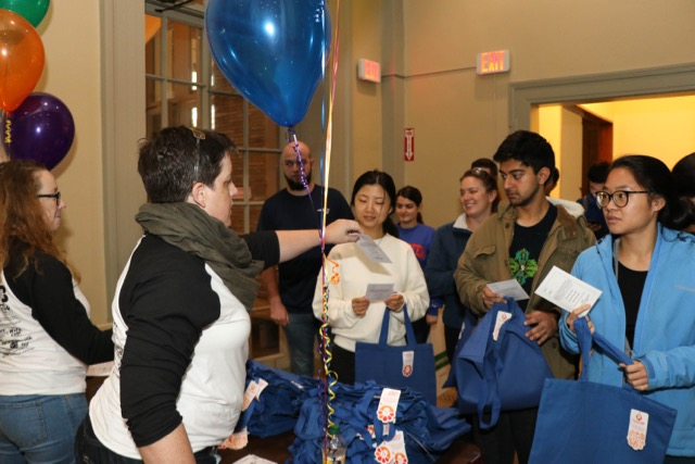 A female staff member distributes tote bags and paper goods to a group of students.