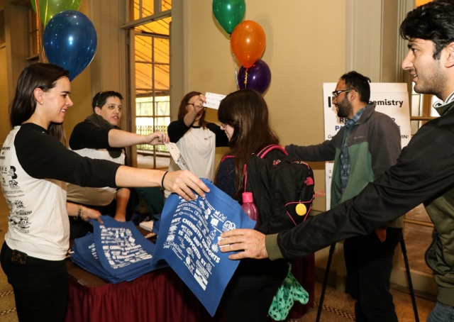 Three female staff members distribute tote bags as students enter a festive event.