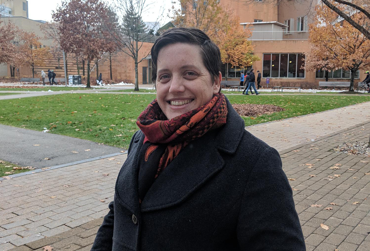 Erin Erhart smiles outdoors in Cambridge on a fall day.