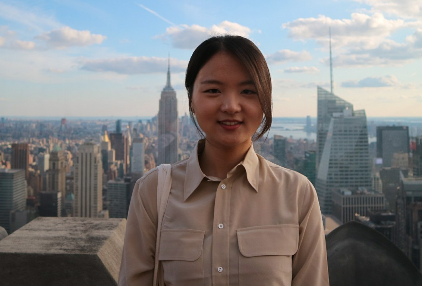 A young woman stands before the New York City skyline.
