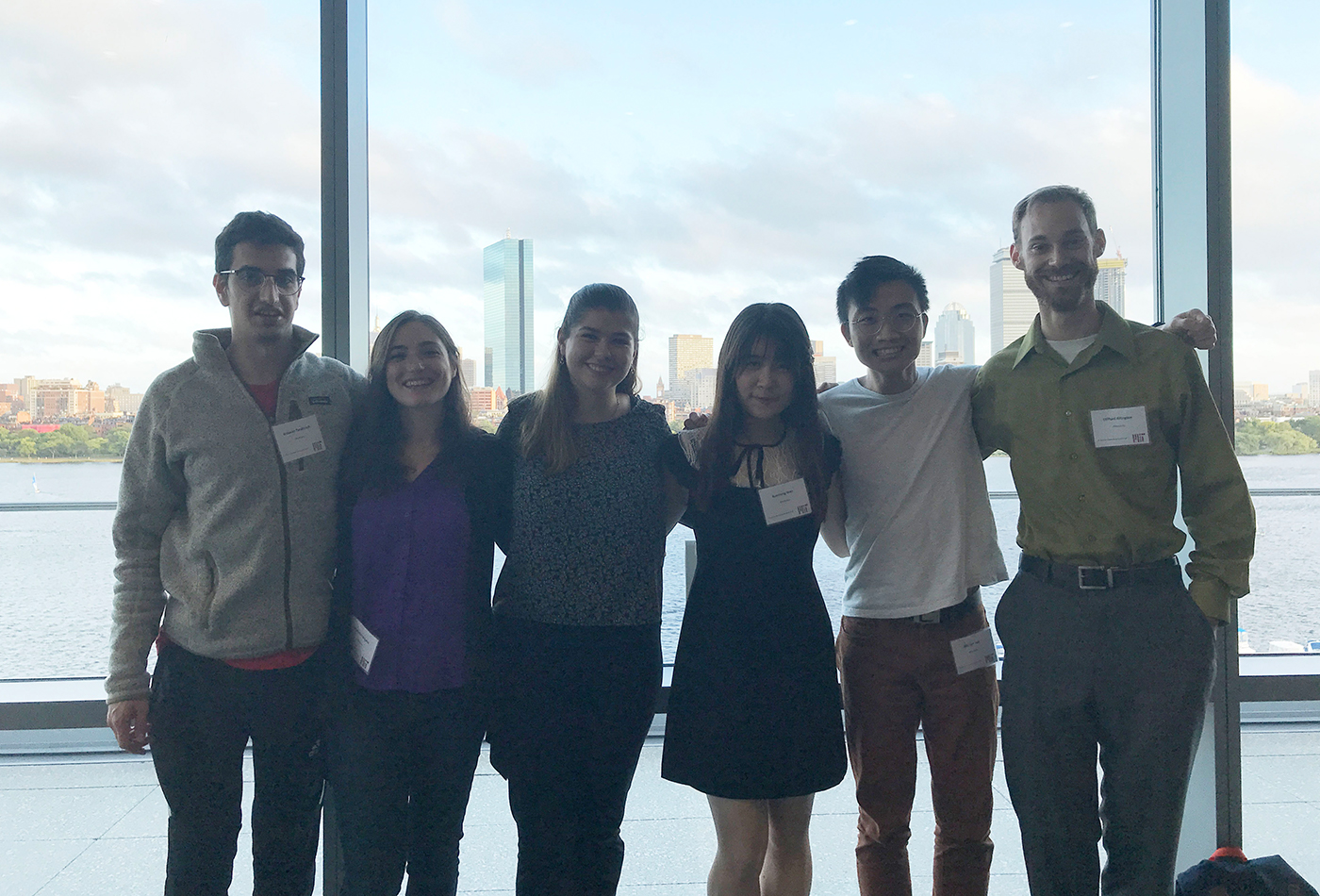 A group of students stands in front of a window featuring the Boston skyline at a reception.