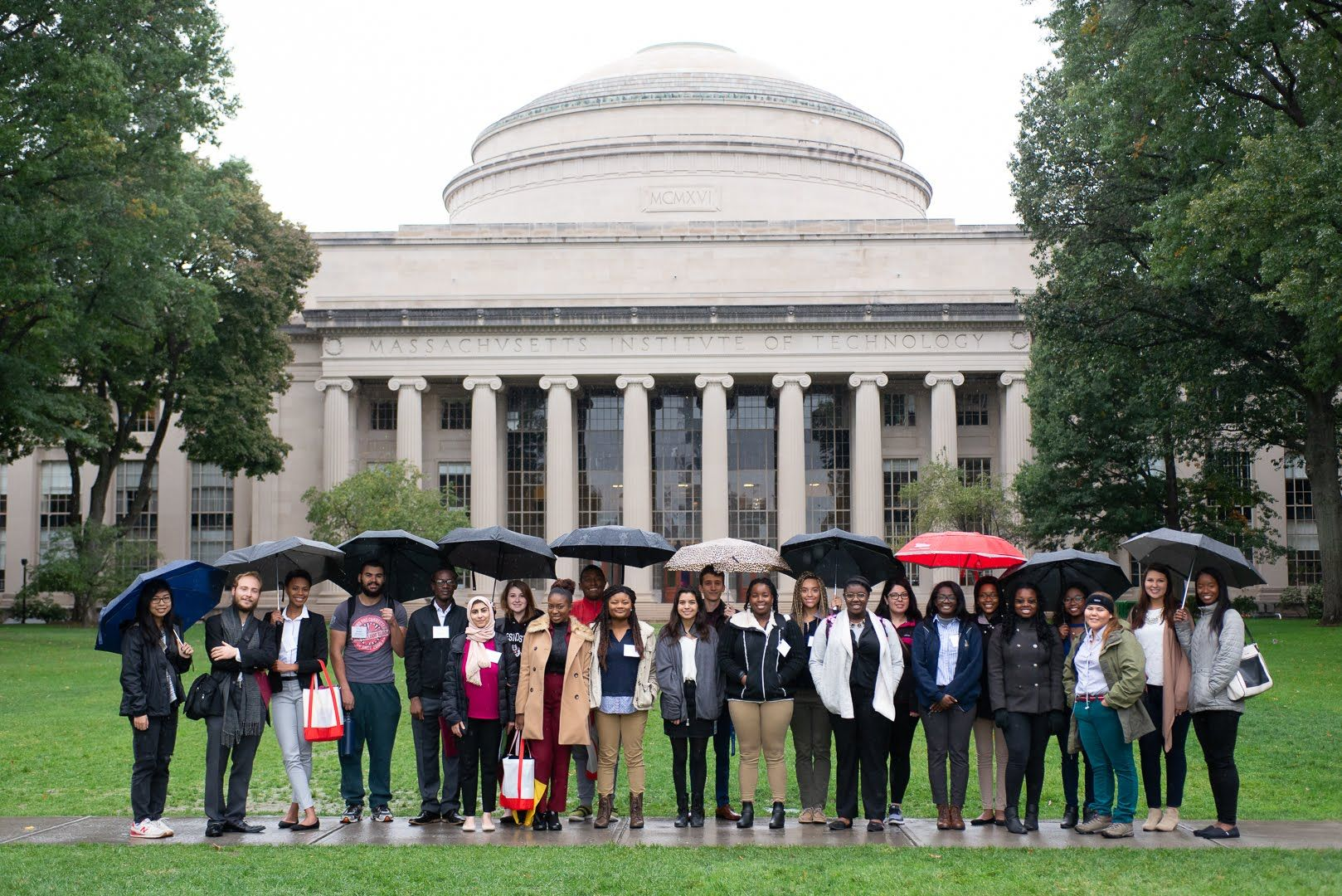 A group of students stands in front of the MIT dome.