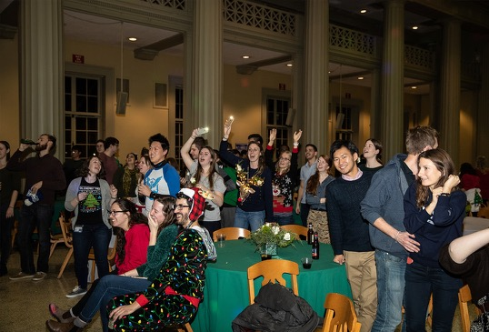 An audience of students enjoys a karaoke performance.