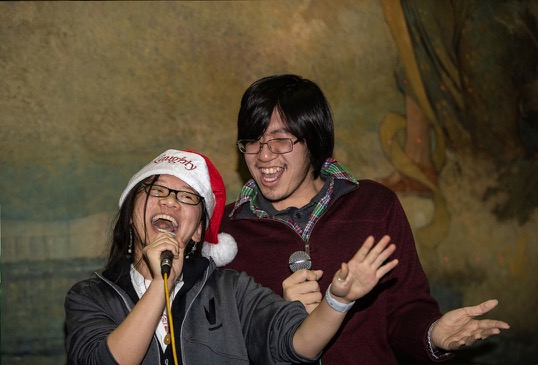 A pair of students enthusiastically performs karaoke.