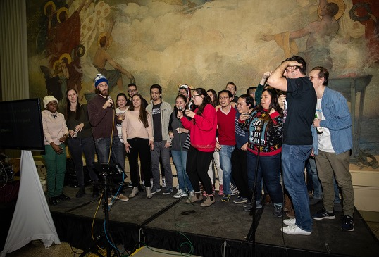 A large group of students perform karaoke on stage.