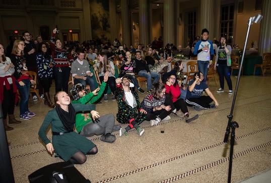 An audience of students enjoys a karaoke performance.