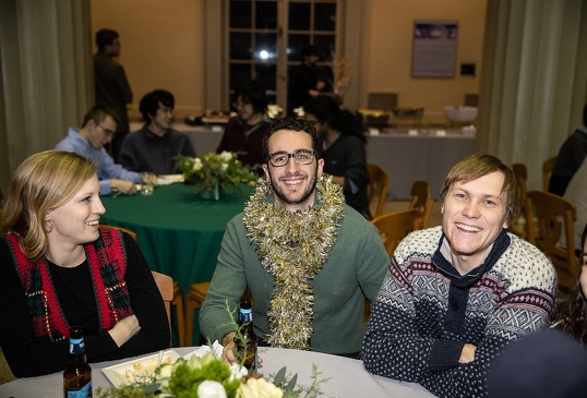 Two festively dressed men and one festively dressed woman sit at a table at a party.