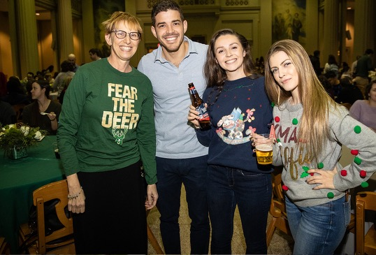 A professor poses with three students and staff members at the holiday party.