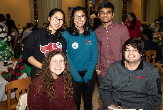 Five students smile for a photo at the holiday oarty.