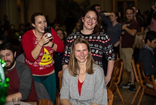 Three women laugh as they enjoy karaoke.