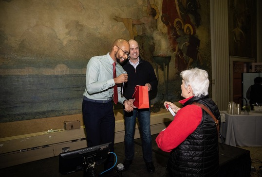 A woman in red collects her raffle prize from two men.