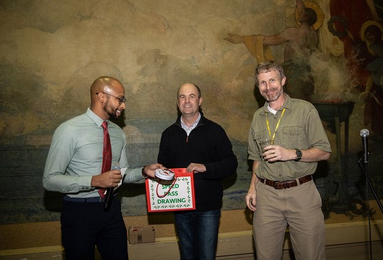 A man collects his raffle prize from two other men.