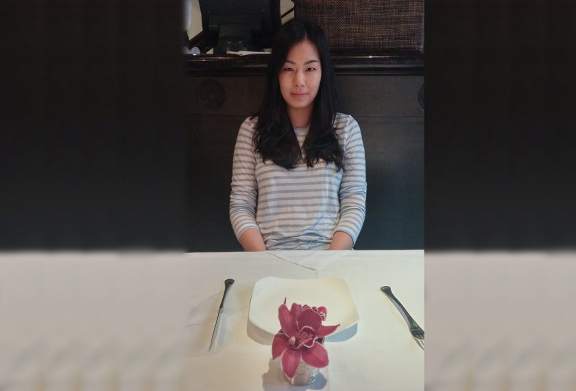 A young woman sits in front of an empty plate in a restaurant