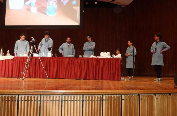Several students in lab coats stand on a stage performing chemistry experiments at a red clothed table.