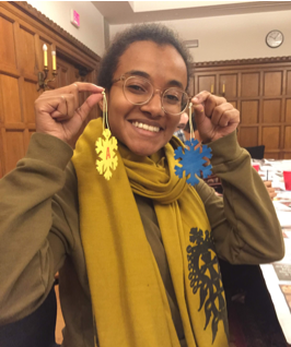 A woman wearing glasses holds up two handmade, bright yellow and blue, snowflake ornaments.