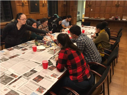 A group of CADI members gather around a newspaper covered table, where they are painting and doing other arts and crafts.
