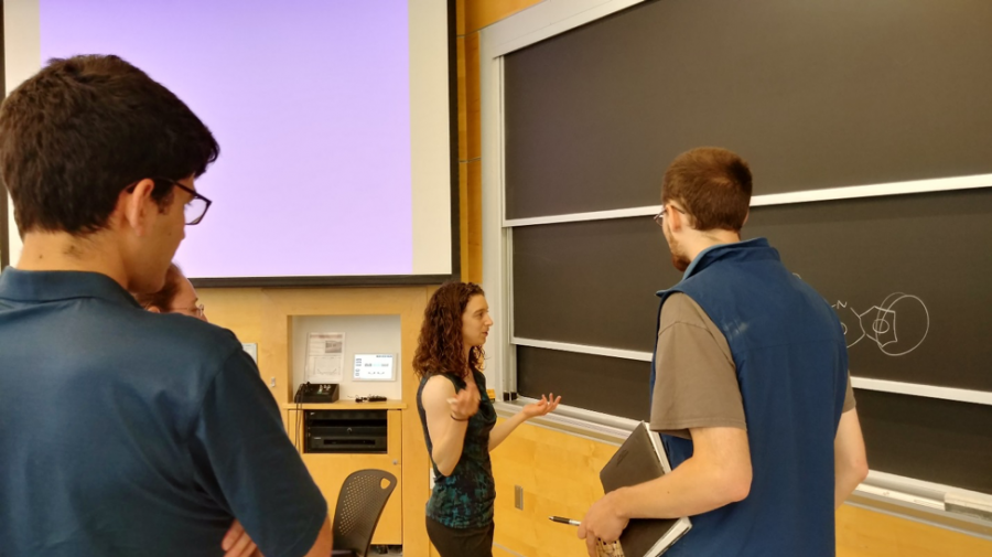 A female student presents a seminar before an audience of fellow students and postdocs.